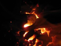 Axe eye in the forge.  The tong jaws are just visible in silhouette on the left side of the eye opening.